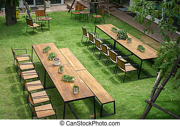 Classic wood with steel rim tables and chairs are arranged in the little garden, shot from 2nd floor.