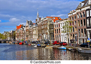 Classical Amsterdam view. Boat floats on the channel on the ...