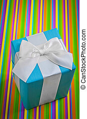 classical blue gift box with white bow on colored striped backgr