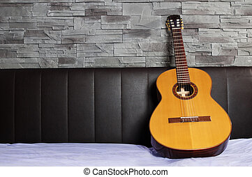 classical guitar lying on the bed in front of a brown...