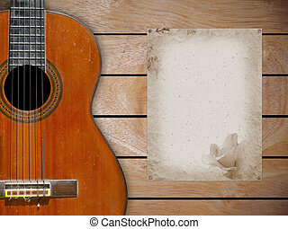 Classical guitar on wood fragment wall with blank page of...