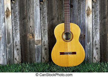 Classical Guitar. - Classical guitar against old fence with...