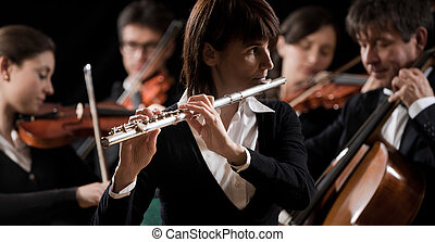 Classical music concert: flutist close-up - Female flutist...