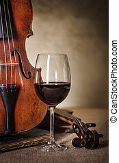 Classical old violin detail with red wine glass