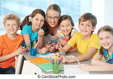 Classmates and teacher - Portrait of joyful schoolkids and...