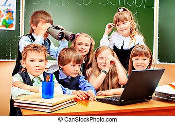 classmates - Happy schoolchildren at a classroom looking...
