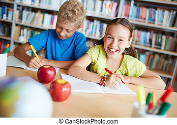 Classmates in library - Portrait of cheerful schoolgirl...