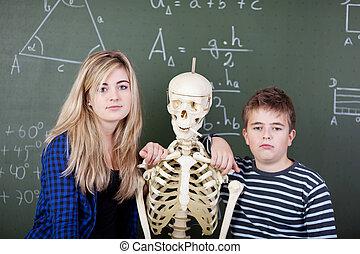 Classmates Leaning On Skeleton Against Blackboard