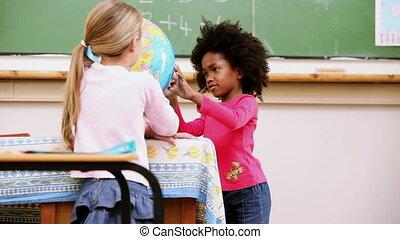 Classmates looking at a globe