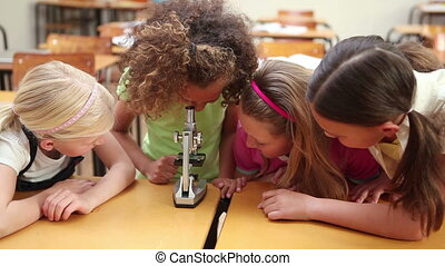 Classmates looking through a microscope in the classroom