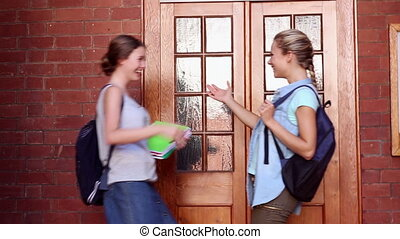 Classmates meeting in hallway and hugging at the university