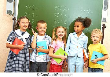 Classmates - Portrait of several kids standing by blackboard...