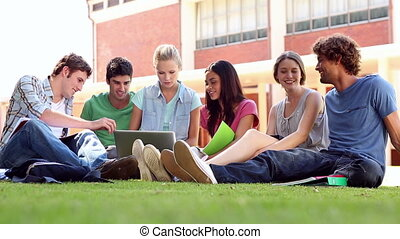 Classmates sitting on the grass chatting at the university