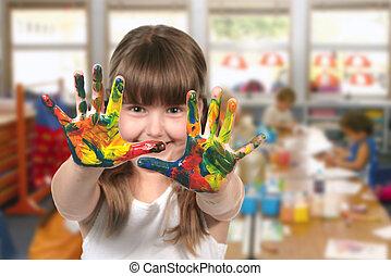 Happy Girl Painting With Her Hands in Kindergarten Class