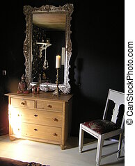 photograph of a part of a well designed black bedroom, showing the chest of drawers and and antique mirror and chair