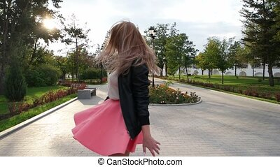 Classy girl dressed in pink skirt turning in the park in ...