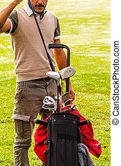 Classy golfer picking a club