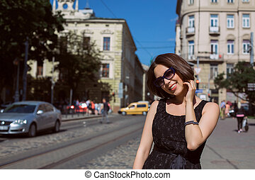 Classy smiling model wearing fashionable dress and glasses walking on the city streets. Empty space