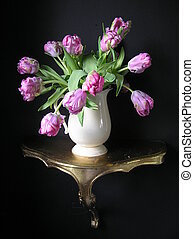 still life photograph of a bouquet with extraordinary multicolored parrot tulips in a white waterpitcher, on top of an antique golden console against a black background, in the tradition of the old dutch masterpaintings