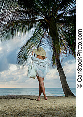 Classy woman on the tropical beach at sunset