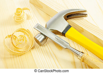claw hammer and chisel on wooden board