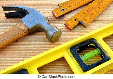 Claw hammer, carpenter meter, water-level on wooden desk background