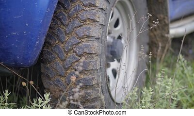 Clay clogged SUV tire, close up.
