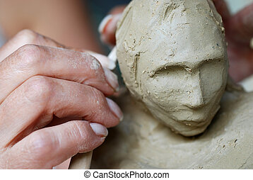 Clay - Close up to a sculptor's hand and female sculpture ...