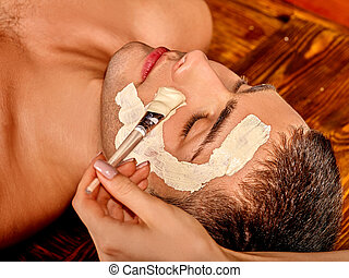 Clay facial mask in beauty spa. - Man getting clay facial...