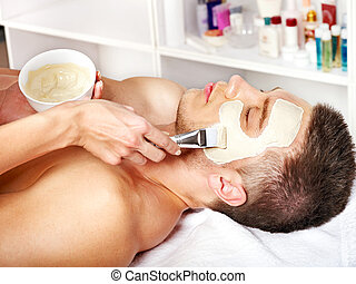 Clay facial mask in beauty spa.