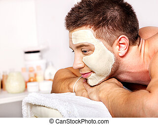 Clay facial mask in beauty spa. - Man with clay facial mask...