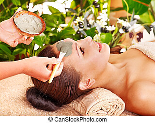 Clay facial mask in beauty spa. - Woman with clay facial...