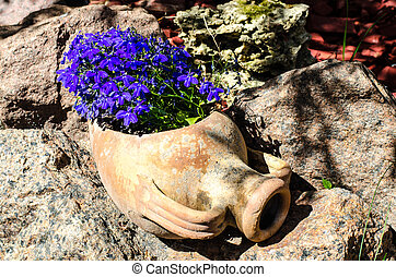 Clay jug of pots with blue flowers