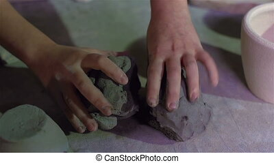 Close-up of a cute schoolgirl taking a clay lump and modeling it