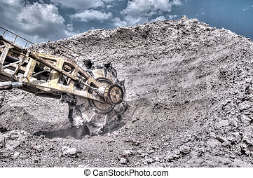 clay mining - A construction vehicle loading clay onto a...