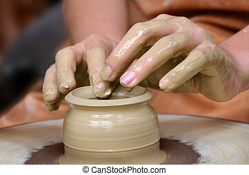 Clay pot on the wheel and two hands