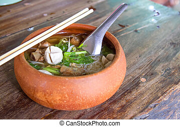 Clay pot rice noodles put on a wooden table