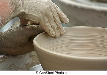 Hands of potter shaping clay pottery bowl