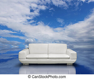 White sofa and silver frames on reflective cloudscape reflection surface