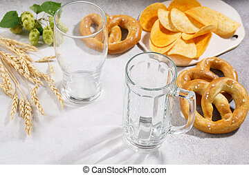 Clean and empty beer glass and a mug with various snacks around.