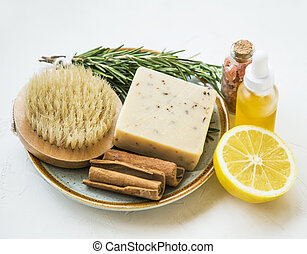 Clean beauty. Natural spa products with rosemary herb, lemon, oil bottle, natural cinnamon soap and brush, natural home skincare products, homespa and wellness clean beauty products