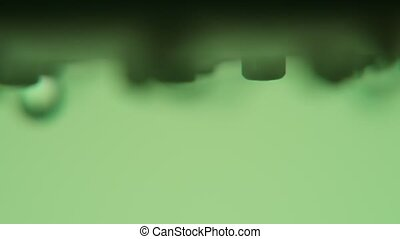 Clean drops of water falling from a metallic nozzle in a...