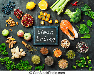 Clean Eating concept. Selection food ingredients and chalkboard with Clean Eating words on dark background. Top view or flat lay.