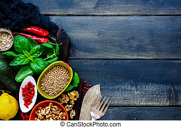Close up of vegan and healthy clean eating cooking ingredients. Goji berries, fresh basil, seeds, green lentils, avocado, spice, lemon over dark rustic background, top view. Detox, dieting or weight loss concept