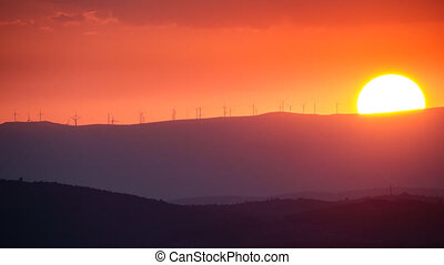 Clean Energy with wind turbines at sunset, time lapse