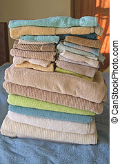 Clean, Folded Towels on a Bed