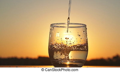 Clean, fresh water poured into a glass at the sunset. Slow motion.