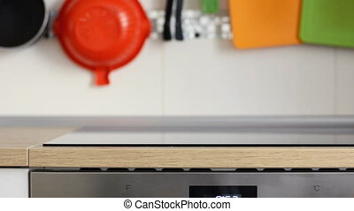Clean kitchen panel with a stove and on the background hang...