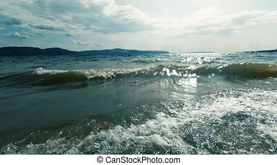 Warm blue sea and small transparent waves. Close-up . In the background mountains and white clouds. Ideal for filling background. Relax and calm.