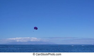 Clean sea water and clear blue sky with someones paragliding